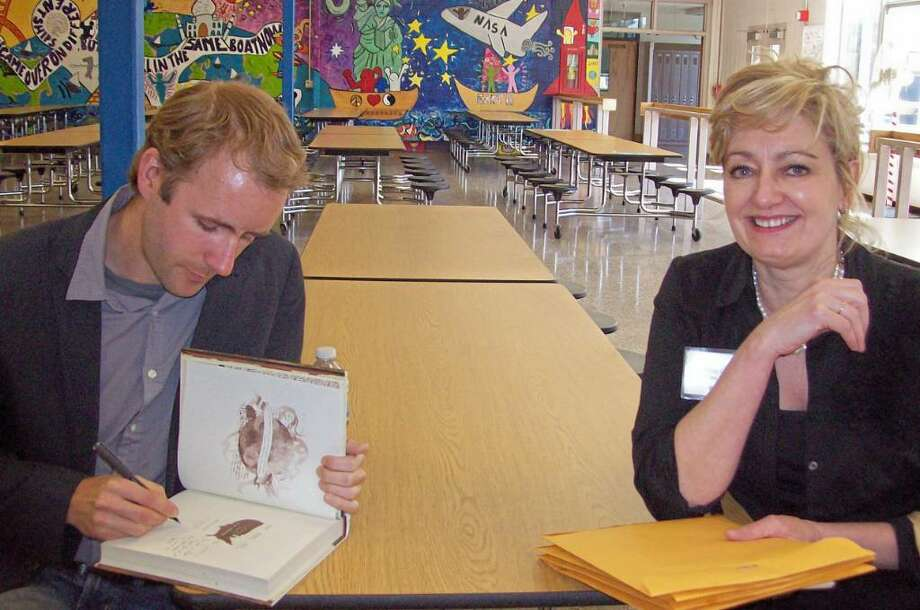 """Jackie Carlino (right) sits with author Reif Larsen as he signs copies of his book """"The Selected Works of T.S. Spivet"""" April 10 at Madison Middle School in Trumbull. Carlino was project director for the Trumbull Library's One Book, One Town program, which tried to get as many residents as possible to read Larsen's book. The library recently won a """"Making a Difference"""" award from the Town of Trumbull Business Education Initiative. Photo: Contributed Photo / Connecticut Post Contributed"""