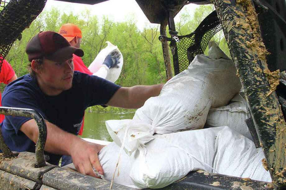 Volunteers and Department of Corrections work crews help Meredosia prepare for flooding that's expected along the Illinois River next week. Photo: Rosalind Essig | Journal-Courier