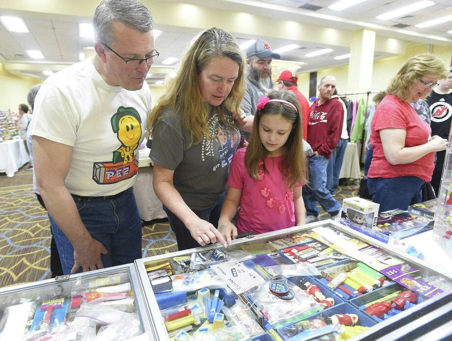 From left, Ken Sinnott of Albany, NY, his wife Kate and 11-year-old daughter Veronica check out a table various collectible PEZ candy dispensers during the 21st annual NEPEZCON and FunkoFest on May 4, 2019 in Stamford, Connecticut. Pez enthusiasts from around New England gather to swap, trade or buy the iconic candy dispensers, with some valued over thousands of dollars. Photo: Matthew Brown / Hearst Connecticut Media / Stamford Advocate