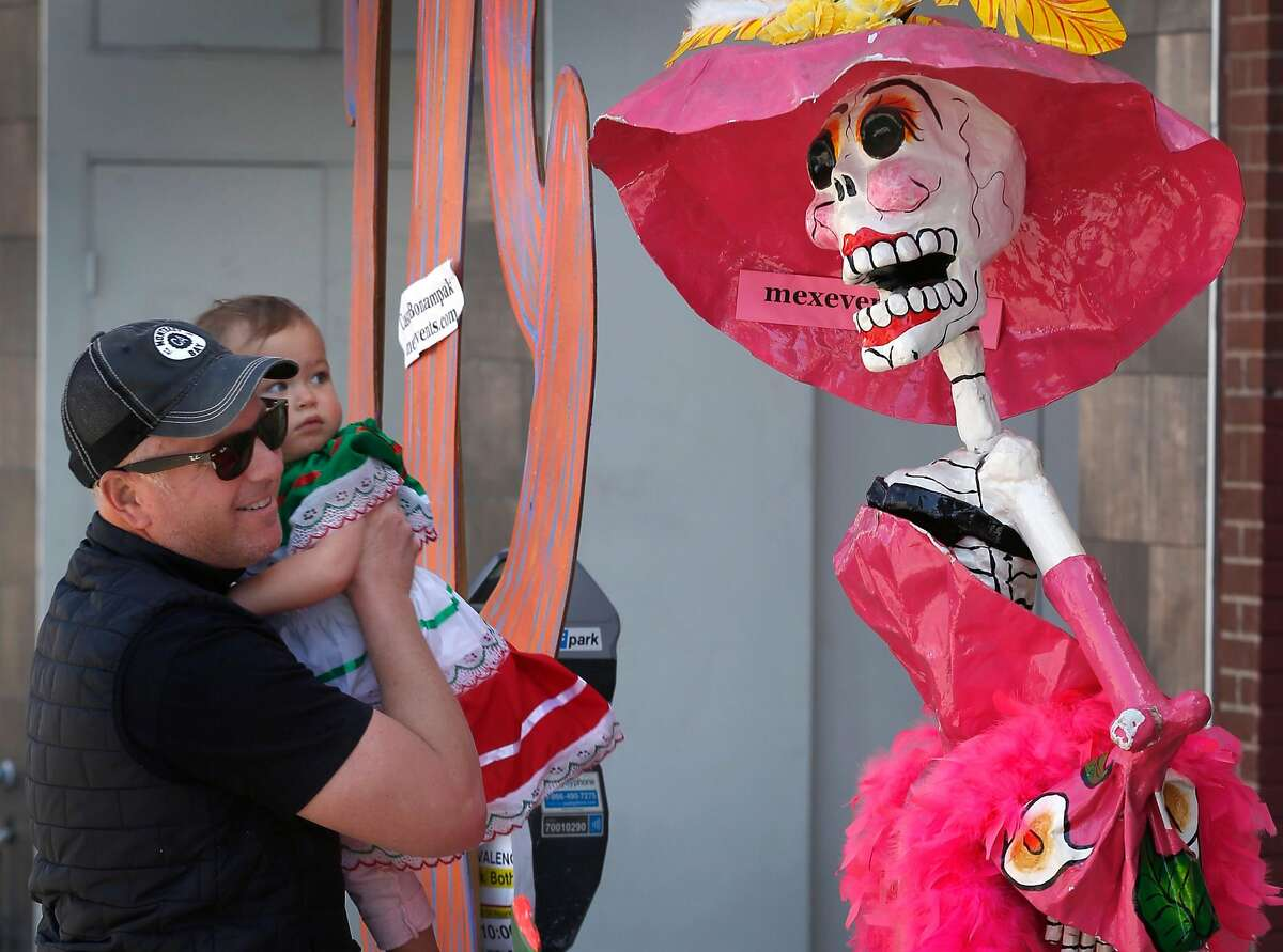 Dave Buchsbaum and his daughter Katherine, 18 months, move in for a close look at a Dia de los Muertos figure at the Cinco de Mayo festival on Valencia Street in San Francisco, Calif. on Saturday, May 4, 2019.