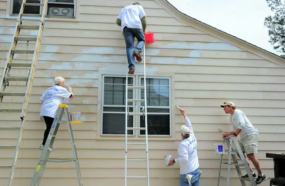 Volunteers from St. Paul's Episcopal Church in Fairfield work to spruce up the home of Angel Maldonado during the 32nd annual HomeFront Day in Bridgeport, Conn., on Saturday May 4, 2019. HomeFront's campaign is to make life-changing repairs to the homes of 60 older adults on fixed incomes, single-parent households, persons with disabilities and families in transitional crisis due to illness or job loss. Photo: Christian Abraham, Hearst Connecticut Media / Connecticut Post