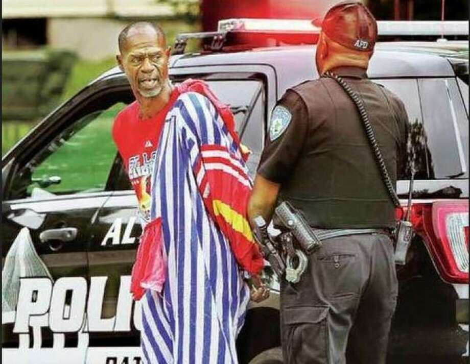 Ron Singleton, dressed in a clown suit he apparently, allegedly, burgled from an abandoned home, is arrested by an Alton police officer after an incident last year. Photo: John Badman | Telegraph File Photo