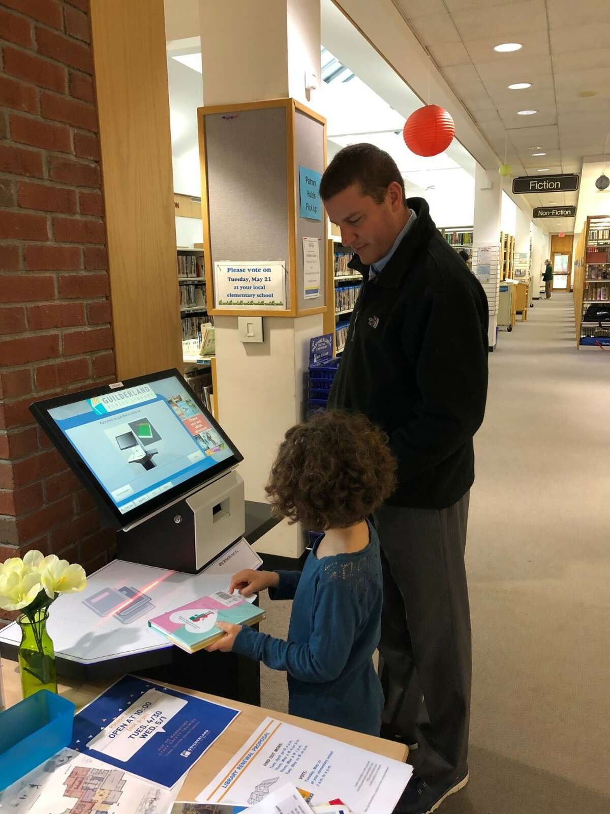 Addison Fisher checks out her children's books while her father, Wade, watches at Guilderland Public Library's self-serve stations. Director Tim Wiles says that since the two stations were installed, 25 percent of all library materials are checked out by patrons via self-service.