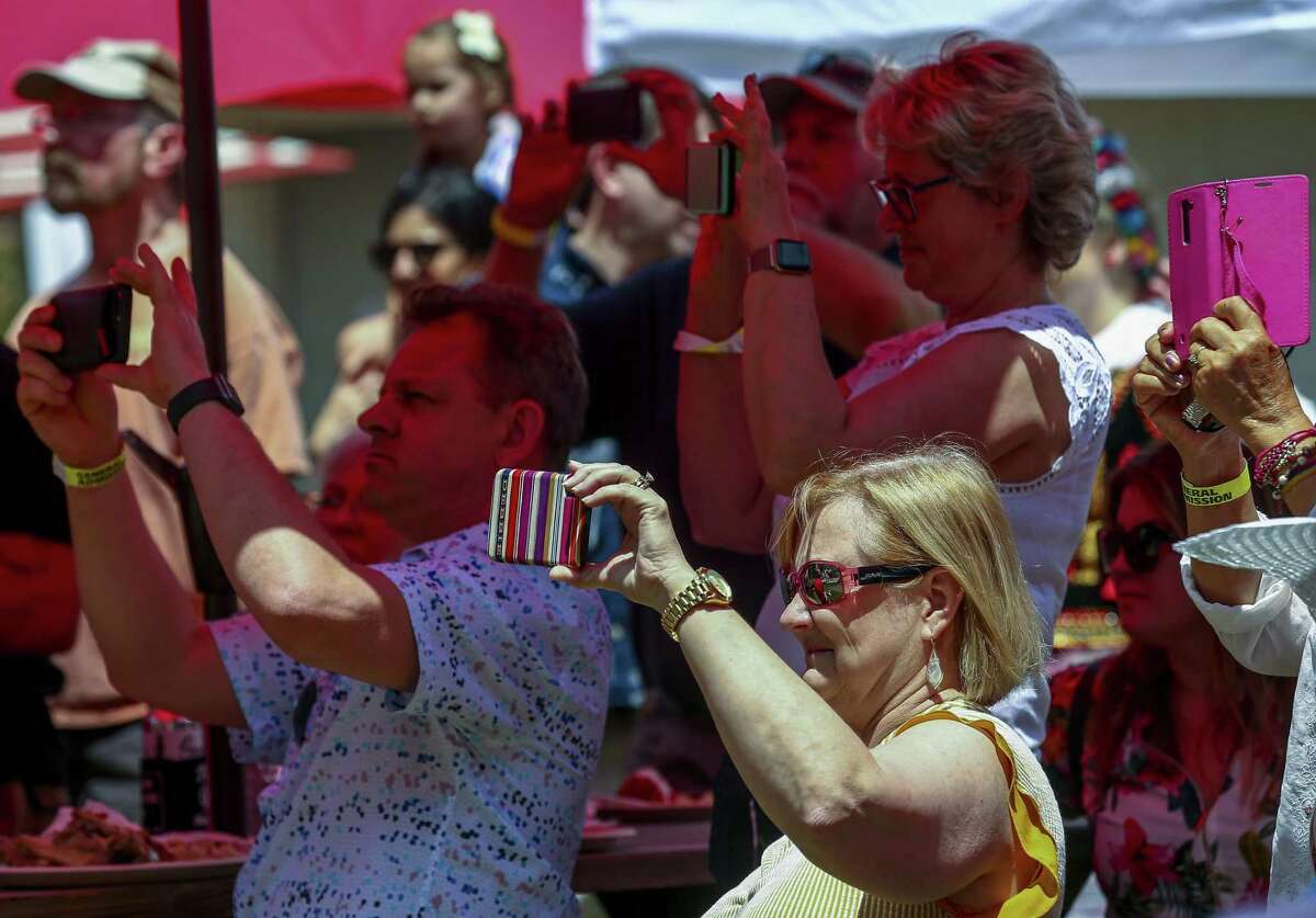 People attending the 13th annual Houston Polish Festival capture a dance performance Saturday, May 4, 2019, in Houston.