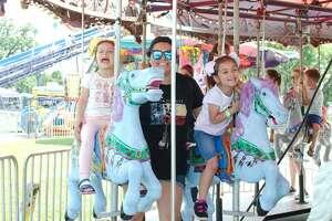 Araceli Moreno, Izabella Dartez and Carly Galicia enjoy a ride on the Merry-Go-Round at the League City Music Festival Saturday, May 4.