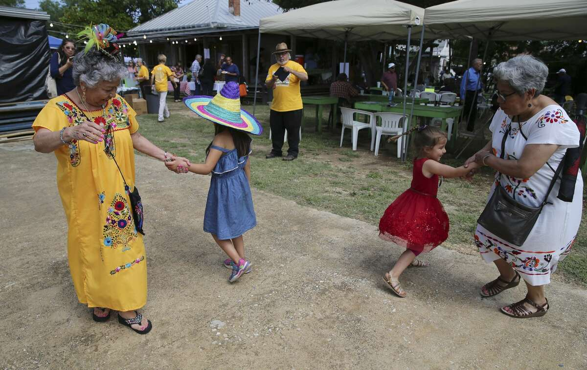 """Olga Martinez (left) dances with six-year-old December Martinez (no relation) as Olivia Cruz (right) dances with her four-year-old granddaughter Mia on Saturday, May 4, 2019 as The Esperanza Peace and Justice Center hosts Paseo por el Westside, a historic and cultural preservation community gathering on the Westside of San Antonio. This year's theme Mi Barrio No Se Vende seeks to highlight the nationwide housing crisis that significantly impacts low income communities like the westside. The yearly celebration highlights the history, culture and people who live there, but this time there's a message to the downtown expansion encroaching on on the area, """"Mi Barrio No Se Vende!"""" which in English means """"My neighborhood is not for sale!"""" (Kin Man Hui/San Antonio Express-News)"""