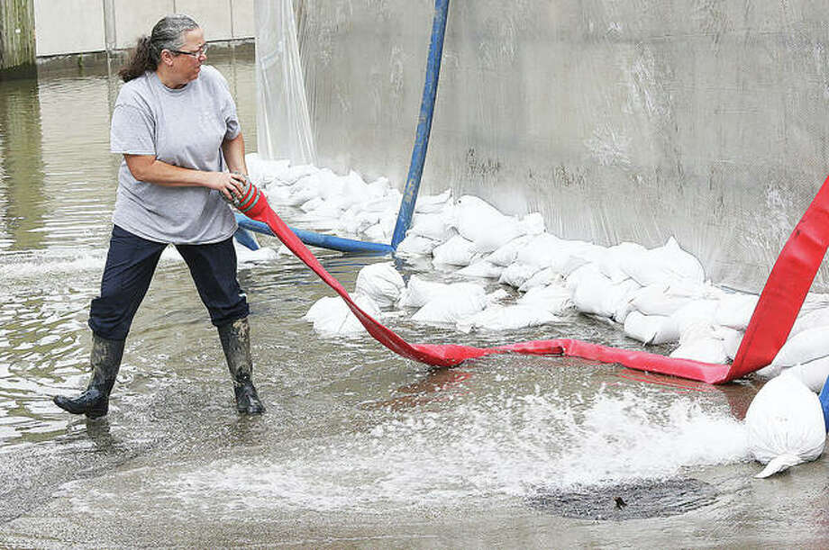 Lisa Morrison, co-owner of Morrison's Irish Pub on State Street in downtown Alton, positions a hose to direct floodwater from the restaurant's basement to the other side of Alton's floodwall Friday.
