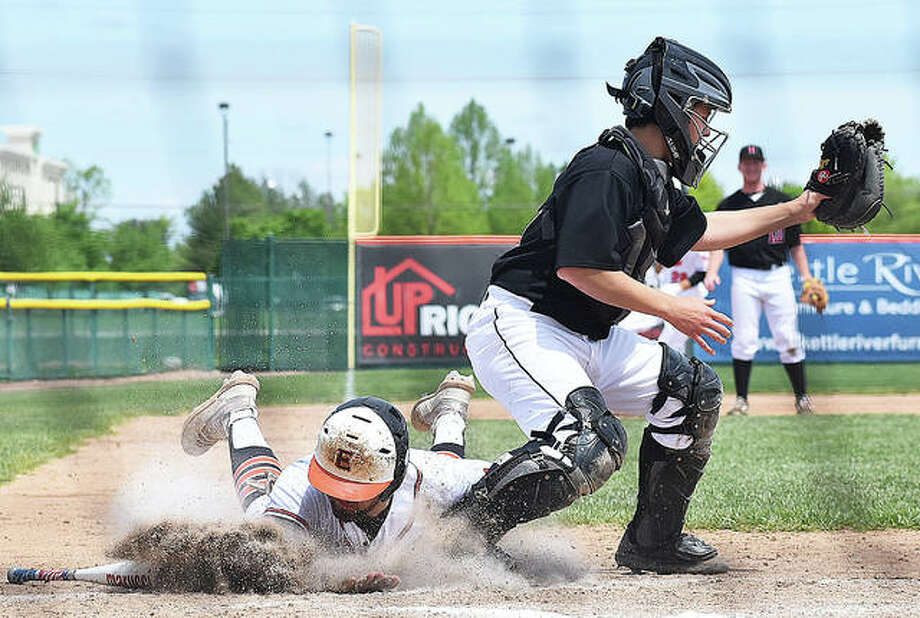 Edwardsville's Max Ringering slides safely into home before the throw in Saturday's game against Highland at Tom Pile Field. Photo: Matt Kamp/The Intelligencer