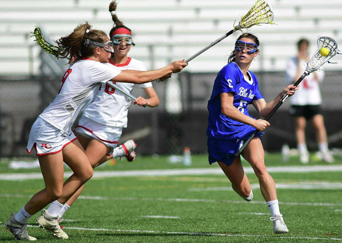 Blue Wave #6 Katie Elders makes her way past Rams #9 Katelyn Sparks and #6 Kaleigh Harden as The No. 1 Darien High School Blue Wave takes on the New Canaan Highh School Rams in their FCIAC girls lacrosse game Saturday. May 4, 2019, in New Canaan, Conn. New Canaan girls lacrosse team defeated the rival Darien Blue Wave 12-11 in the Class L semifinals last spring.