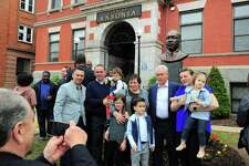 The family of sculptor Vasil Rakaj, second from right, pose together with him in front of the bust of Martin Luther King Jr. that he created, after it was unveiled in front of Ansonia City Hall in Ansonia, Conn., on Saturday May 4, 2019.
