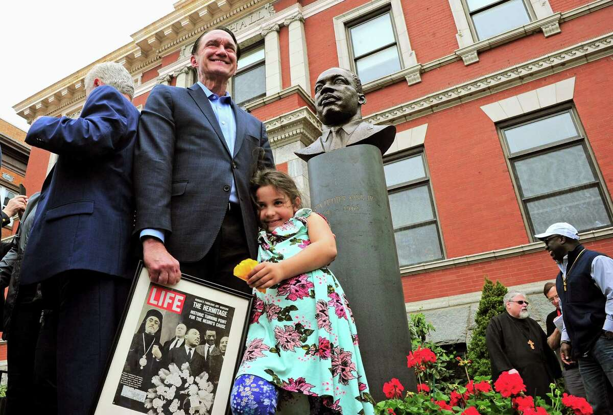 Greg Stamos holds a framed Life magazine cover as he stands with his granddaughter Parela, 7, in front of the bust of Martin Luther King Jr. that was unveiled in front of Ansonia City Hall in Ansonia, Conn., on Saturday May 4, 2019.