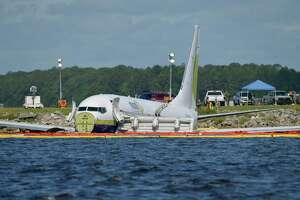 A charter plane carrying 143 people and traveling from Cuba to north Florida sits in a river at the end of a runway, Saturday, May 4, 2019 in Jacksonville, Fla.  The Boeing 737 arriving at Naval Air Station Jacksonville from Naval Station Guantanamo Bay, Cuba, with 136 passengers and seven aircrew slid off the runway Friday night into the St. Johns River, a NAS Jacksonville news release said.  (Will Dickey/The Florida Times-Union via AP)