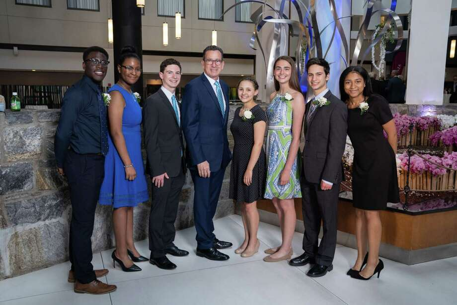 Former Gov. Dannel Malloy, fourth from left, was honored as Stamford Citizen of the Year Tuesday at the Crowne Plaza Stamford, along with scholarship winners, from left, Eliel Duquene, Claudia Lucien, Samuel Diamond, Shayna Druckman, Lauren Klym, Jacob Herz and Maureen Ferrer. The event is co-sponsored by the City of Stamford and Jewish War Veterans, Fred Robbins Post 142. Photo: HappyHaHa.com