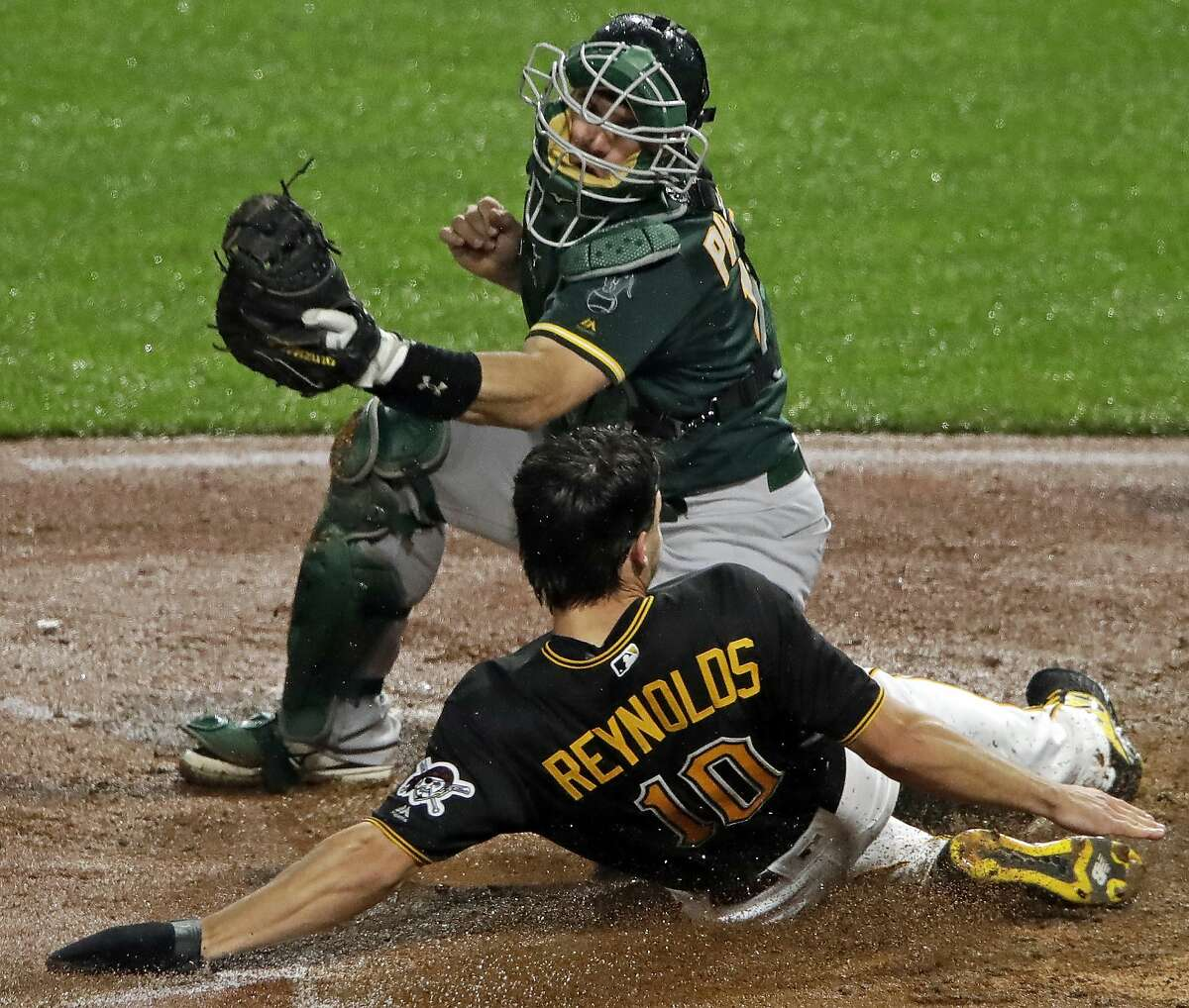 Pittsburgh Pirates' Bryan Reynolds (10) scores ahead of the tag by Oakland Athletics catcher Josh Phegley, the second of two runs on a double by Kevin Newman off Athletics relief pitcher J.B. Wendelken during the seventh inning of a baseball game in Pittsburgh, Saturday, May 4, 2019. (AP Photo/Gene J. Puskar)