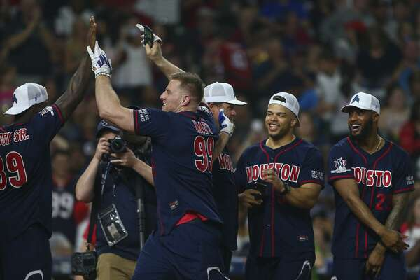 Houston Texans defensive lineman J.J. Watt celebrates with teammates after scoring against the offense during the J.J. Watt Foundation Charity Classic at Minute Maid Park Saturday, May 4, 2019, in Houston. The foundation's mission is to provide funding for middle schools across the country that have insufficient or no funding for after-school athletic programs.