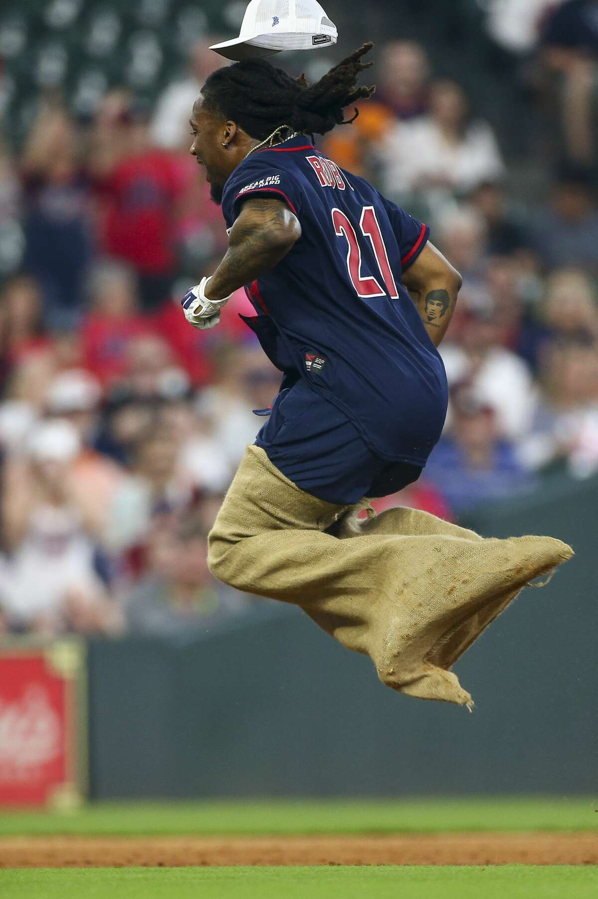 Houston Texans cornerback Bradley Roby competes in a sack race against the defense during the J.J. Watt Foundation Charity Classic at Minute Maid Park Saturday, May 4, 2019, in Houston. The foundation's mission is to provide funding for middle schools across the country that have insufficient or no funding for after-school athletic programs.