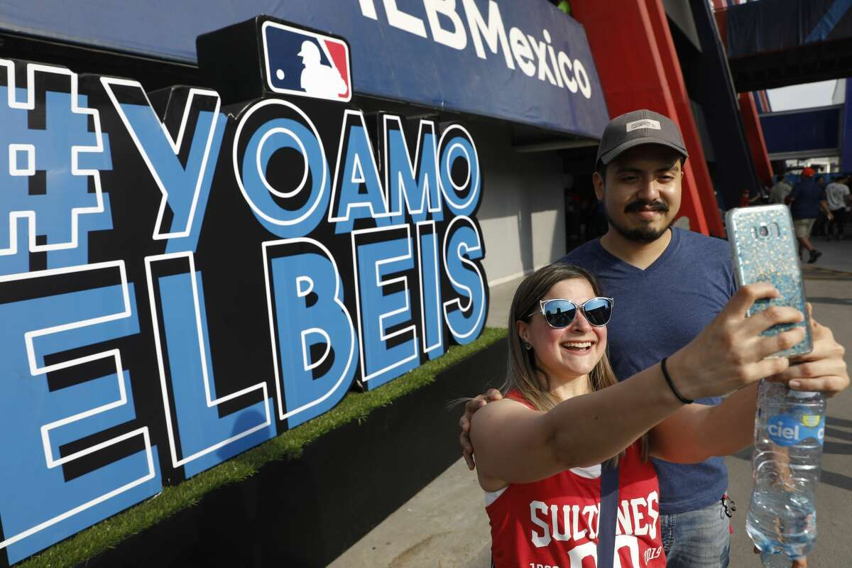 """Fans take a selfie in front of a sign that reads, in Spanish, """"I love baseball,"""" as they arrive for a baseball game between the Houston Astros and the Los Angeles Angels, in Monterrey, Mexico, Saturday, May 4, 2019. (AP Photo/Rebecca Blackwell)"""
