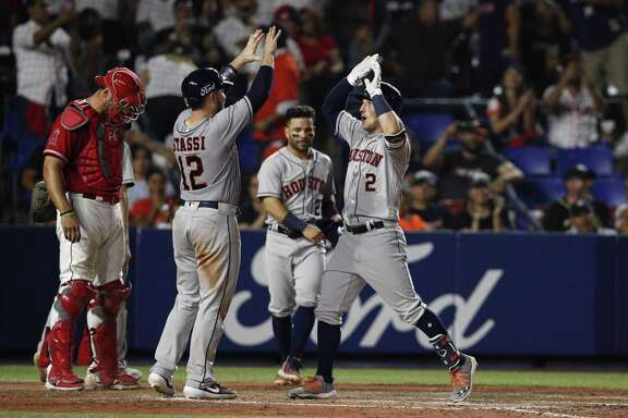 Alex Bregman, right, is congratulated by teammate Max Stassi after hitting a home run in the eighth inning against the Angels on Saturday in Monterrey, Mexico. Bregman also homered in the first inning and finished 3-for-5 with four runs batted in.
