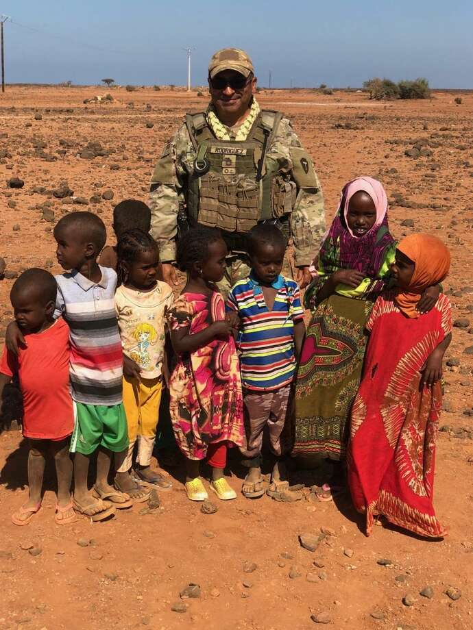 Sgt. 1st Class Robert Rodriguez, a platoon sergeant for the 1st Battalion, 141st Infantry Regiment, 72nd Infantry Brigade Combat Team, 36th Infantry Division of the Texas Army National Guard, stands with several of the children in Djibouti. Rodriguez gifted 500 sandals to barefoot orphans and children during their deployment. Rodriguez coordinated the sandal donation effort with his daughter's school, The Blessed Sacrament in Laredo, Texas. Photo: Capt. Nadine Wiley De Moura /Texas Joint Counterdrug Task Force