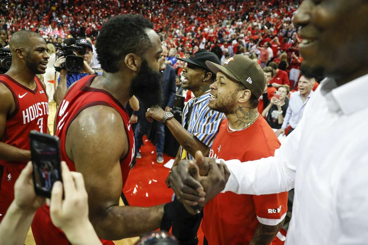 Houston Rockets guards James Harden (13) and Chris Paul (3) celebrate the Rockets win with Travis Scott and other fans during overtime of Game 3 of a NBA Western Conference semifinal playoff game at Toyota Center, in Houston , Saturday, May 4, 2019.
