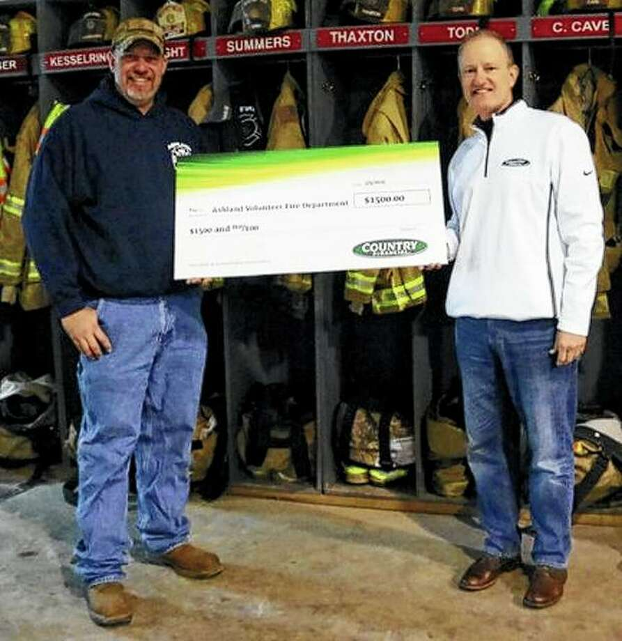 Rick Pettit (right) of Country Financial presents a $1,500 donation to Ashland Volunteer Fire Department Chief Tyler Lathom as part of Country Financial's Operation Helping Heroes program. The funds will help the department buy new plastic extrication cribbing equipment, which is used to stabilize a vehicle while removing a victim trapped inside. The new equipment will replace the wooden cribbing blocks the department has used in the past. Photo: Photo Provided