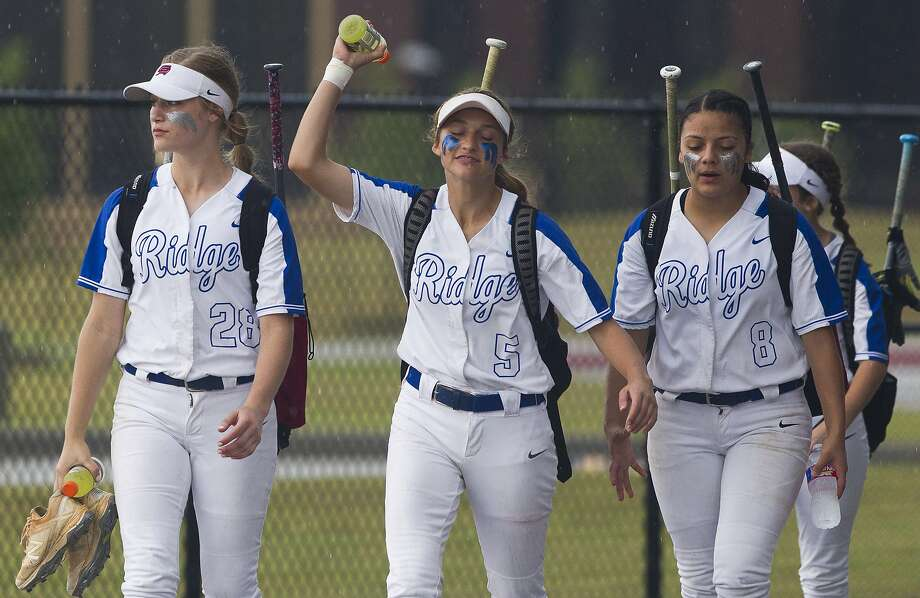Oak Ridge's Mackenzie Ward, center, reacts beside teammates Marissa Mason, left, and Alexia Villegas as the team faces another weather delay during Game 1 of Region II-6A area high school softball playoff series at Grand Oaks High School, Friday, May 3, 2019, in Spring. Photo: Jason Fochtman, Staff Photographer