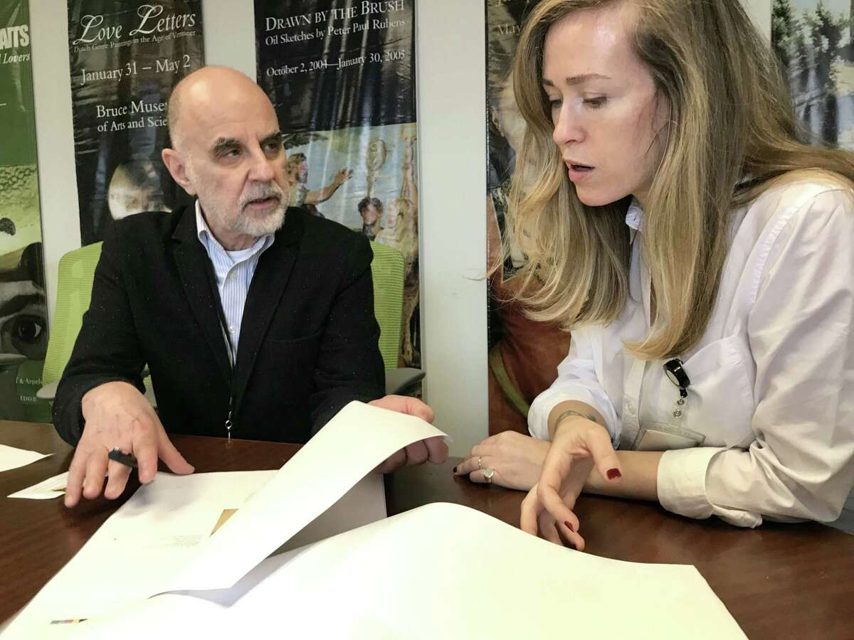"""Curator Kenneth E. Silver and Assistant Curator Stephanie Guyet review the catalog that will accompany the """"Summer with the Averys"""" exhibition at the Bruce Museum in Greenwich."""