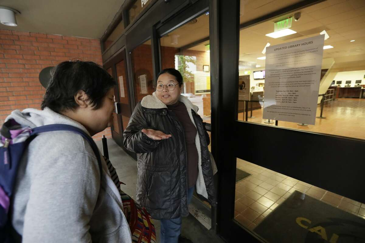 FILE - Sophornia Ko, left, and Marie Choi (who is blind) arrive at John F. Kennedy Memorial Library at Cal State LA that was closed Friday morning, April 26, 2019. A person with a confirmed measles case visited the library at Cal State L.A. on April 11. Seventy-one students and 127 staff members were quarantined at California State University, Los Angeles after a possible measles exposure at a campus library.