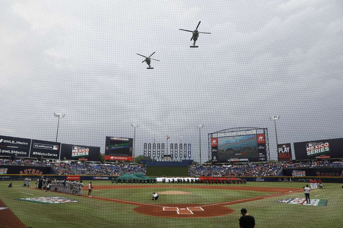 Helicopters fly over the stadium at the start of a baseball game between the Los Angeles Angels and Houston Astros, in Monterrey, Mexico, Sunday, May 5, 2019. (AP Photo/Rebecca Blackwell)wld
