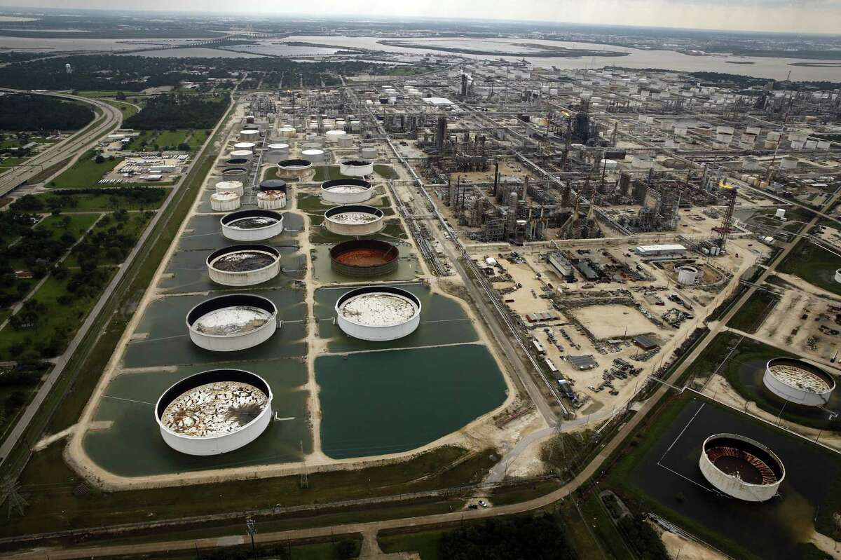 FILE - In this Wednesday, Aug. 30, 2017 file photo, large storage tanks situated in retention ponds are surrounded by rainwater left behind by Tropical Storm Harvey at ExxonMobil's refinery in Baytown, Texas. Companies have reported that roughly two dozen storage tanks holding crude oil, gasoline and other fuels collapsed or otherwise failed during Harvey, spilling a combined 140,000 gallons of fuel, according to an Associated Press analysis of state and federal accident databases. Federal rules require companies to be prepared for spills, but don't require them to take any specific measures to secure the massive fuel storage tanks at refineries and oil production sites that are prone to float and break during floods. (Tom Fox/The Dallas Morning News via AP, file)