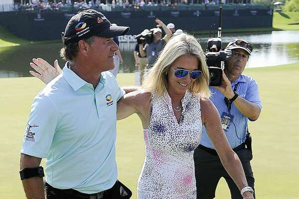 Scott McCarron, left, walks off the #18 green with wife, Jenny, after winning the Insperity Invitational golf tournament, Sunday, May 5, 2019, in The Woodlands, TX.