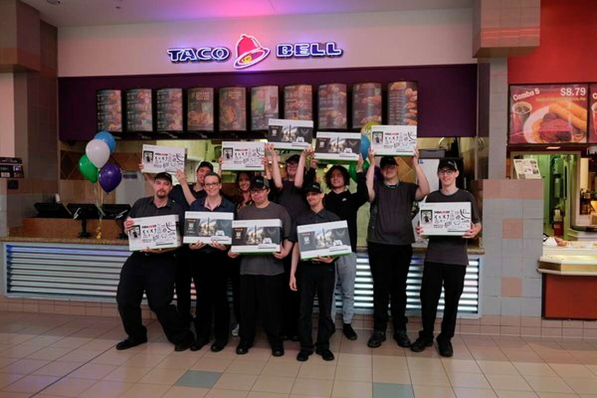 Employees of the Taco Bell in the Midland Mall hold their new Xbox One S with Taco Bell's No. 1 regional general managerof the year and Golden Bell recipient Jennifer Avery (backrow, center).The Xbox Ones were a gift to each member of the team at the Midland Mall location as a thank you from Mariane Inc. (Photoprovided by Darla Bowen, Mariane Inc.)