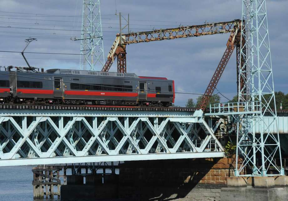 A northbound Metro-North train passes across the railroad bridge spanning Cos Cob Harbor in the Cos Cob section of Greenwich, Conn. Tuesday, Oct. 25, 2016. The 1904 movable bridge did not close properly after it opened to allow river traffic to pass Tuesday morning, causing delays for commuters aboard the New Haven line trains. Photo: Tyler Sizemore / Hearst Connecticut Media / Greenwich Time