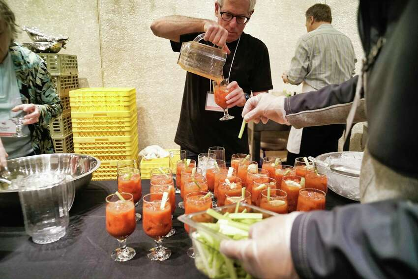 Volunteer Ed Flink pours a Bloody Mary into a glass for people at the Capital Roots' 32nd Annual Spring Brunch at the Empire State Plaza Convention Center on Sunday, May 5, 2019, in Albany, N.Y. Over 600 people came out to enjoy food featuring dishes and desserts donated by more than 125 local restaurants. The brunch is the largest event in terms of community involvement for the organization and all the work at the brunch is done by volunteers. Capital Roots will hold their Spring Plant Sale on May 18th at the Urban Grow Center in Troy. Capital Roots, which runs 12 different programs, will be opening two new gardens in Albany and is working on a new Veggie Mobile to replace the current one. Capital Roots has 54 gardens in four counties, helping 4,000 people grow food for their families. (Paul Buckowski/Times Union)