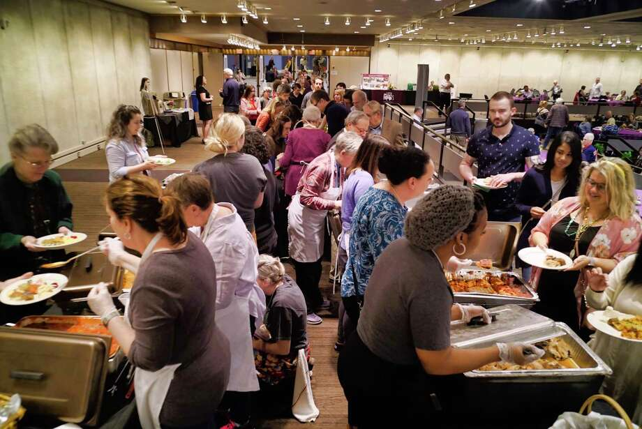Volunteers dish out food at the Capital Roots' 32nd Annual Spring Brunch at the Empire State Plaza Convention Center on Sunday, May 5, 2019, in Albany, N.Y. Over 600 people came out to enjoy food featuring dishes and desserts donated by more than 125 local restaurants. The brunch is the largest event in terms of community involvement for the organization and all the work at the brunch is done by volunteers. Capital Roots will hold their Spring Plant Sale on May 18th at the Urban Grow Center in Troy. Capital Roots, which runs 12 different programs, will be opening two new gardens in Albany and is working on a new Veggie Mobile to replace the current one. Capital Roots has 54 gardens in four counties, helping 4,000 people grow food for their families.  (Paul Buckowski/Times Union) Photo: Paul Buckowski / (Paul Buckowski/Times Union)