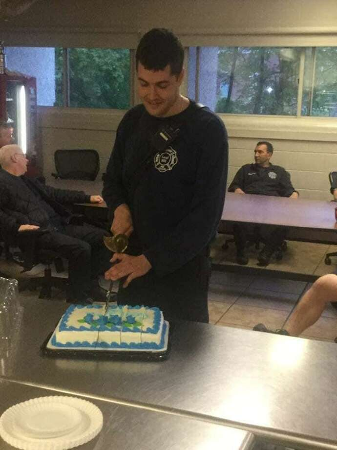 Firefighter Daniel Mansdorf cuts a cake during his farewell party at Danbury Fire Department headquarters Saturday. Photo: Danbury Fire Department / Facebook
