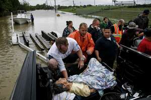 A rescuer moves Paulina Tamirano, 92, from a boat to a truck bed as people evacuate from the Savannah Estates neighborhood as Addicks Reservoir surpasses capacity due to near constant rain from Hurricane Harvey Tuesday, Aug. 29, 2017 in Houston.