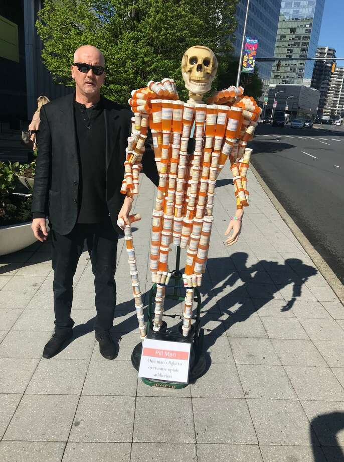 Frank Huntley standing outside of Purdue Pharma on Tresser Boulevard with his sculpture, Pillman,, which he made out of nearly 300 pill bottles that he was perscribed over a 15-year period by a doctor. Huntley said the pills are dangerous and addictive. Photo: John Nickerson / Staff