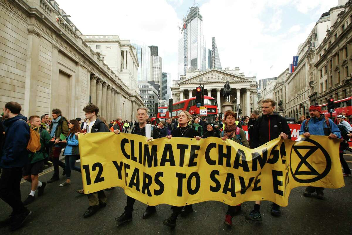 """Climate activists from the Extinction Rebellion group demonstrate during protests outside the Bank of England in the City of London, U.K., on Thursday, April 25, 2019. The demonstrators are demanding that the U.K. acknowledge the """"crisis"""" posed by global warming, enact legally binding policies to reduce net carbon emissions to zero by 2025, and form a citizens assembly to oversee changes. Photographer: Luke MacGregor/Bloomberg"""