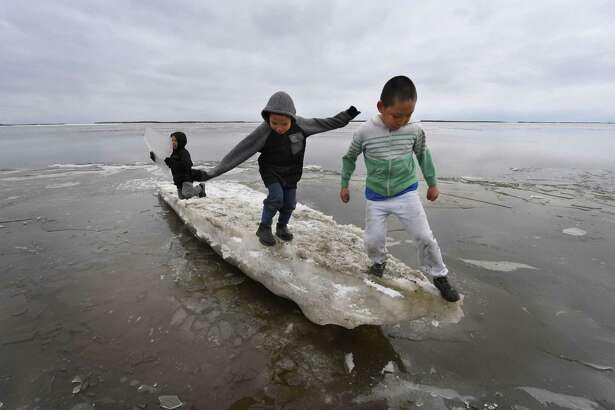 """Schoolchildren play on melting ice at the climate change affected Yupik Eskimo village of Napakiak on the Yukon Delta in Alaska on April 18, 2019. - With recent unusually high temperatures life in this remote villages has been affected causing eroded land, flooding, and difficulties to access roads and to hunting. Local leaders are also mulling moving the entire village of 700 people to safer grounds. """"From 1901 to 2016, average temperatures in the mainland United States increased by 1.8 degrees Fahrenheit (one degree Celsius), whereas in Alaska they increased by 4.7 degrees,"""" said Rick Thoman, a climate expert with the Alaska Center for Climate Assessment and Policy. According to a 2009 report by the Government Accountability Office, the majority of the state's more than 200 native villages are affected by erosion and flooding, with 31 facing """"inminent threats"""". (Photo by Mark RALSTON / AFP)MARK RALSTON/AFP/Getty Images"""