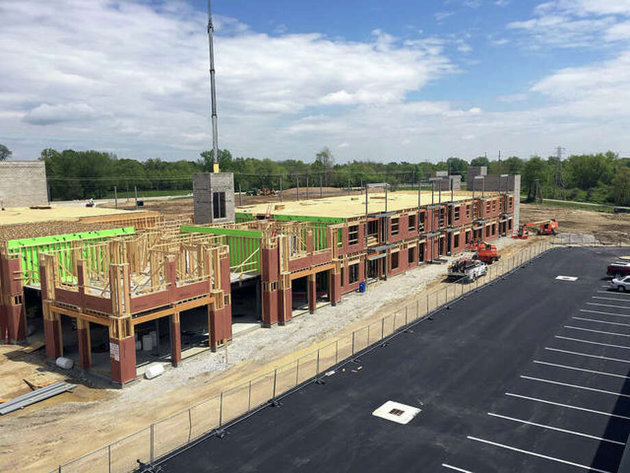 This aerial shot shows the residential construction framing on the second level, the stairway and elevator towers and the back side of of the parking lot for Kloss Furniture. Photo: Photos Courtesy Of BAM Marketing