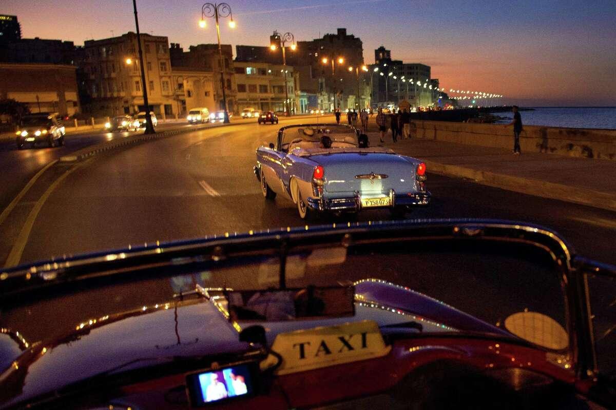 Convertible taxis drive along the Malecon in Havana, Cuba.