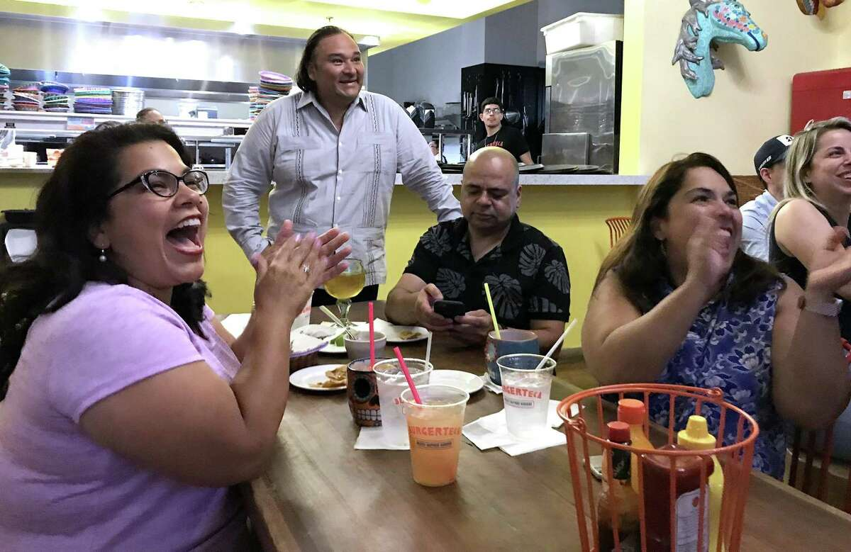 """Fans and supporters of San Antonio chef Johnny Hernandez (standing) gather at his Southtown restaurant Burgerteca to watch Hernandez's Cinco de Mayo appearance on the Food Network show """"Beat Bobby Flay."""""""