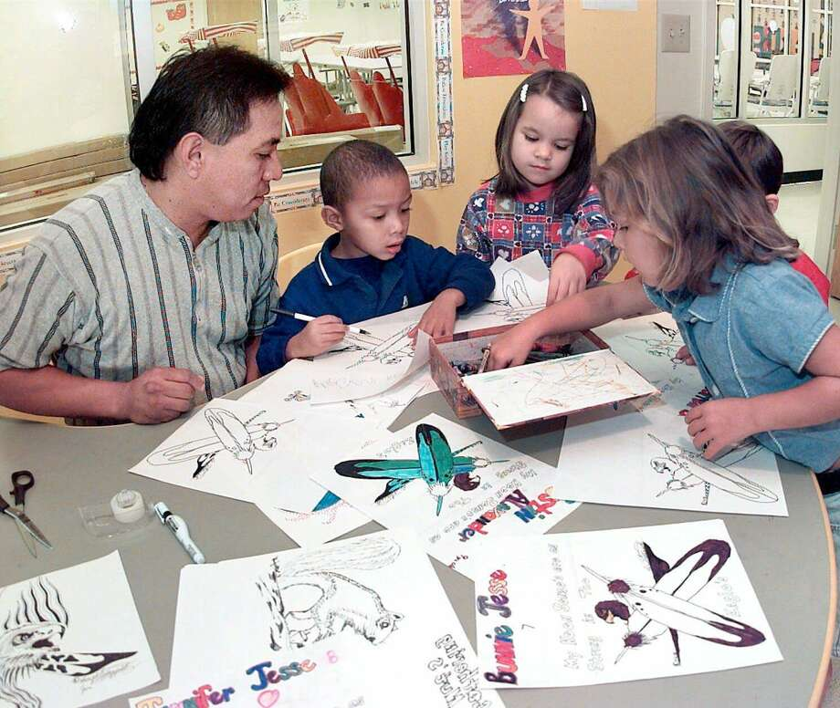 Art teacher Robert Satterfield discusses eagles and feathers in 1998, with children at the Creek Nation day care center in Okmulgee, Okla. The welfare of such children who are up for adoption is at the heart of the Indian Child Welfare Act, which Congress should act to preserve. At its core, the ICWA helps keep Native American children within their families, communities and heritage. Photo: STEPHEN PINGRY /AP / TULSA WORLD