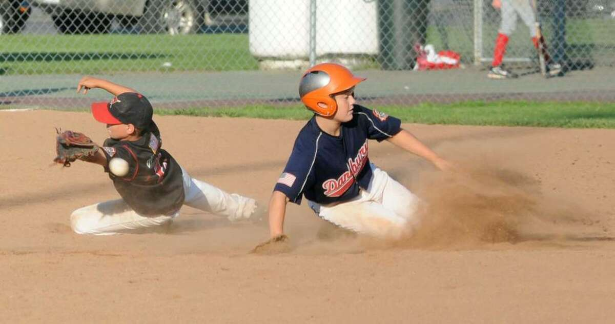 Rocco Swenson, right, of the Danbury Dynamite is called safe after Troy Dunnam, left, of the New Cannan Cannons, misses a throw during a Cal Ripken, 11 year old league, state tournament game, against New Cannan, on Tuesday, July 27, 2010, at Rogers park in Danbury.