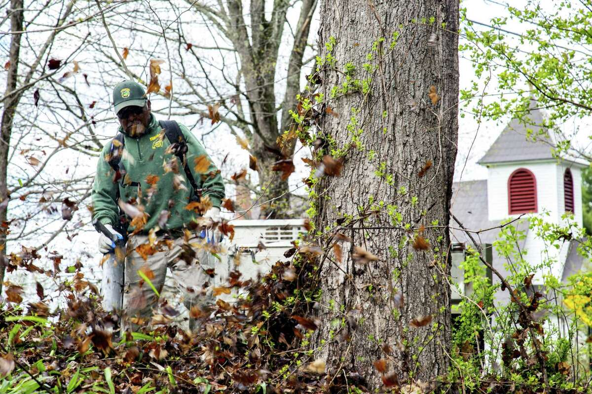 Florentino Barrera-Hernandez blows leaves at Merryall Center for the Arts. He was one of 38 volunteers from YardApes, Inc, a landscaping company in New Milford, that spruced up various nonprofits on April 28, 2019.
