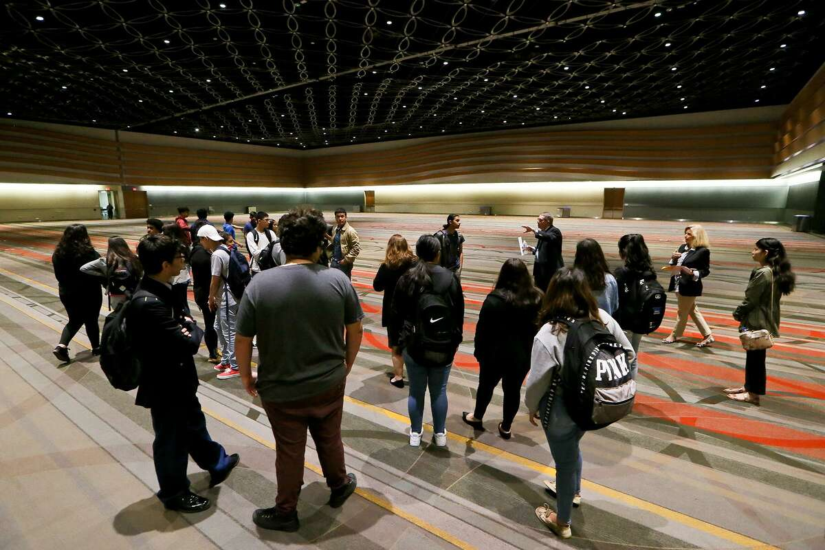Jeff Cook, top, with the Convention Center, talks to the Memorial High School hospitality and tourism class inside the Stars at Night Ballroom, the largest ballroom in Texas at 54,000 square feet, during a tour on Wednesday, May 1, 2019. Memorial High School in the Edgewood ISD is the first in the city to have a hospitality course program approved by TEA and the Texas Workforce Commission.