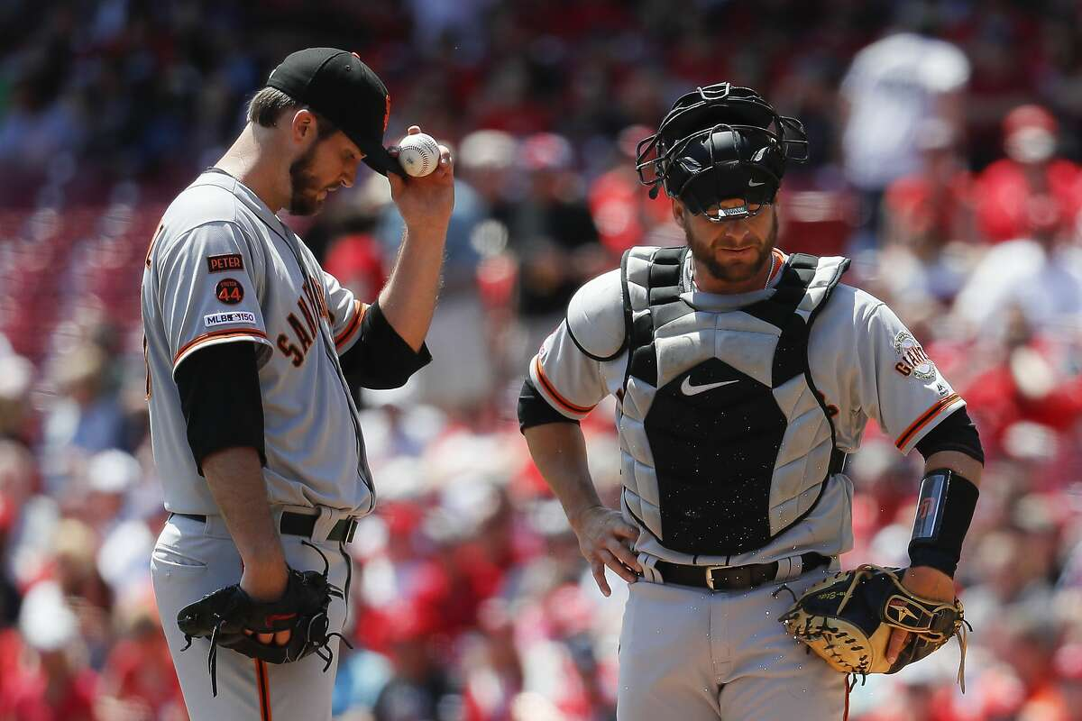 San Francisco Giants starting pitcher Drew Pomeranz, left, and catcher Stephen Vogt, right, react in the first inning of a baseball game against the Cincinnati Reds, Monday, May 6, 2019, in Cincinnati. (AP Photo/John Minchillo)