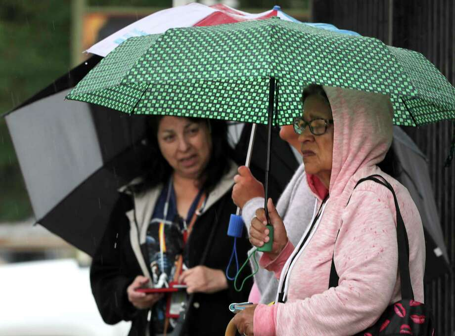 """Elizabeth Serna, right, and Maria V. Hernandez, left, peek out from under their umbrellas as they wait for a bus on McCullough Ave, on Monday, May 6, 2019. Hernandez said, """"I just want to get home and get out of this weather"""". Photo: Bob Owen, Staff Photographer / ©2019 San Antonio Express-News"""