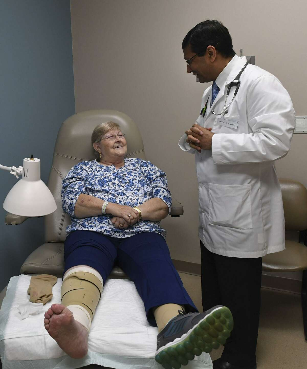 JoAnn Sanchez chats with Dr. Jayesh Shah about her foot wounds at the Wound Care Center at Northeast Baptist Hospital. Shah used a dermaPACE shockwave system to help promote healing of her wounds.